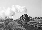An unidentified ex-LMS 2-8-0 8F locomotive is seen coupled to a brakevan as it approaches the bank past Kingsbury Colliery
