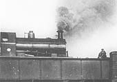Close up showing the 0-4-0ST which is working hard as it crosses over the bridge at the head of the short train